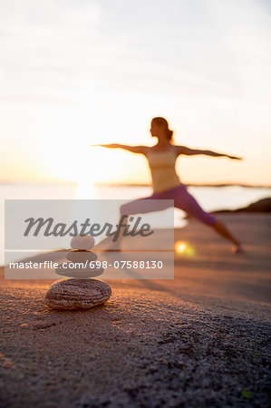 Woman practicing yoga warrior pose on lakeshore with focus on stack of stones Stock Photo - Premium Royalty-Free, Image code: 698-07588130