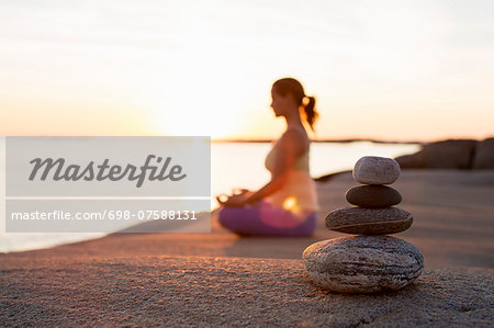 Side view of woman sitting in lotus position on lakeshore with focus on stack of stones Stock Photo - Premium Royalty-Free, Image code: 698-07588131