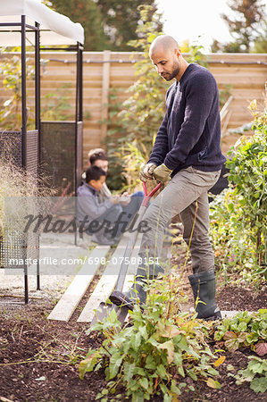 Man digging in garden with children in background Stock Photo - Premium Royalty-Free, Image code: 698-07588151