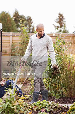 Mature man gardening at yard with children in background Stock Photo - Premium Royalty-Free, Image code: 698-07588152