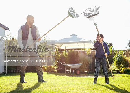 Father and son fighting with rakes at yard Stock Photo - Premium Royalty-Free, Image code: 698-07588173