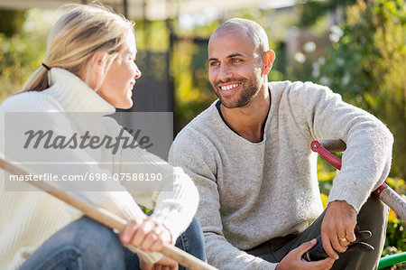 Mature couple with gardening equipment sitting at yard Stock Photo - Premium Royalty-Free, Image code: 698-07588190