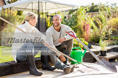Full length of mature couple with gardening equipment sitting at yard Stock Photo - Premium Royalty-Free, Image code: 698-07588191