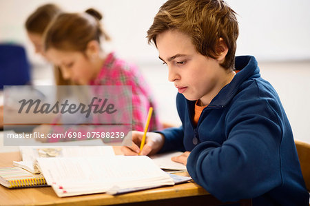 High school students studying at desk in classroom Stock Photo - Premium Royalty-Free, Image code: 698-07588239