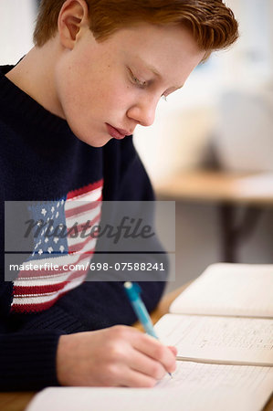 High school boy writing at desk in classroom Stock Photo - Premium Royalty-Free, Image code: 698-07588241