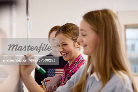 Happy school girls writing on whiteboard in classroom Stock Photo - Premium Royalty-Free, Image code: 698-07588253