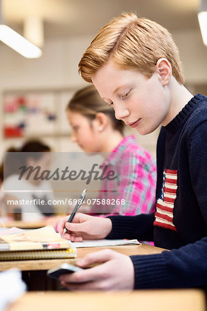 High school student using mobile phone while studying in classroom Stock Photo - Premium Royalty-Free, Image code: 698-07588268