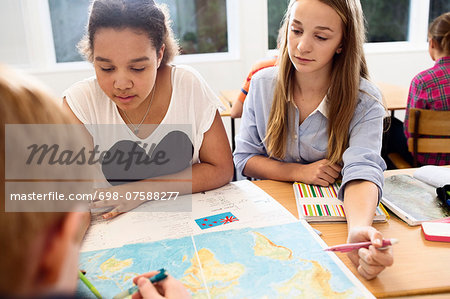 High school students studying map at desk Stock Photo - Premium Royalty-Free, Image code: 698-07588277
