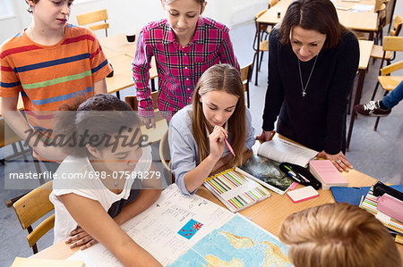 High angle view of teacher and students studying map at desk in classroom Stock Photo - Premium Royalty-Free, Image code: 698-07588279