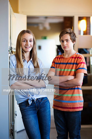Portrait of confident high school students standing arms crossed in locker room Stock Photo - Premium Royalty-Free, Image code: 698-07588295
