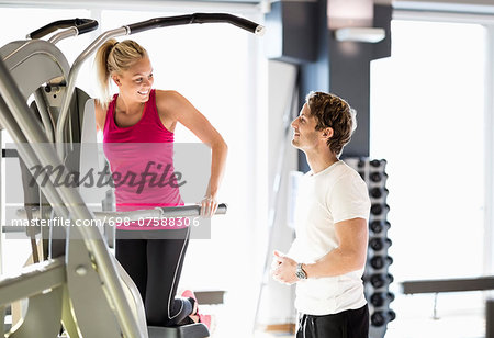 Instructor talking to customer exercising at gym Stock Photo - Premium Royalty-Free, Image code: 698-07588306