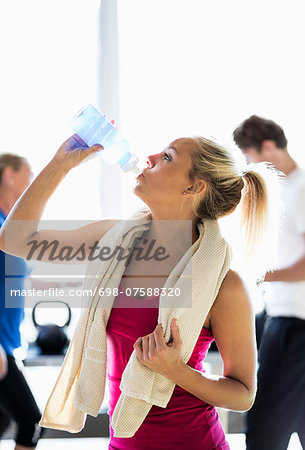 Fit young woman drinking water at health club Stock Photo - Premium Royalty-Free, Image code: 698-07588320