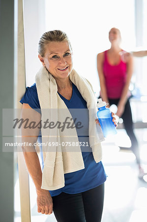 Portrait of fit senior woman with towel and water bottle standing at gym Stock Photo - Premium Royalty-Free, Image code: 698-07588321