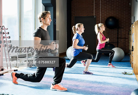 Customers exercising with kettlebells at gym Stock Photo - Premium Royalty-Free, Image code: 698-07588327