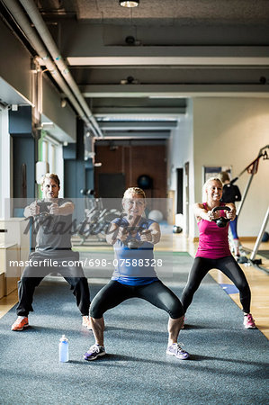 Full length of friends lifting kettlebells at health club Stock Photo - Premium Royalty-Free, Image code: 698-07588328