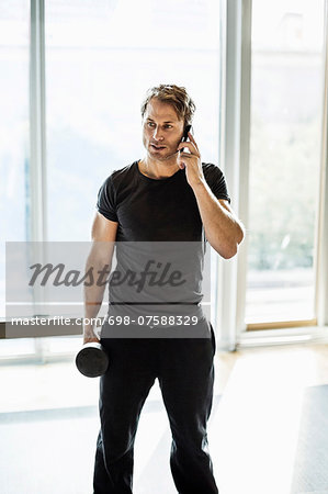 Man using mobile phone while exercising at gym Stock Photo - Premium Royalty-Free, Image code: 698-07588329