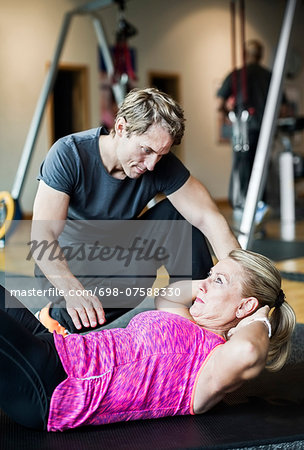 Male instructor assisting senior woman in doing sit-ups at gym Stock Photo - Premium Royalty-Free, Image code: 698-07588330