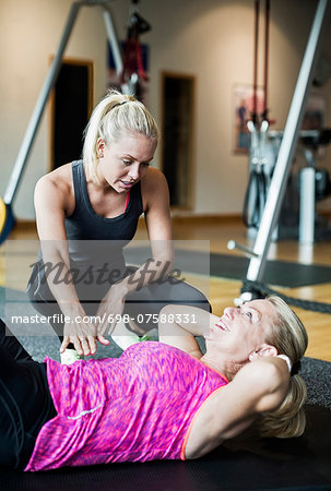 Female instructor assisting senior woman in doing sit-ups at gym Stock Photo - Premium Royalty-Free, Image code: 698-07588331