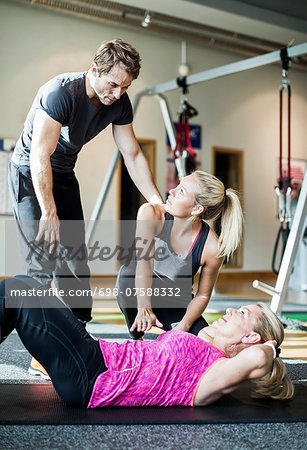 Instructors with senior woman doing sit-ups at health club Stock Photo - Premium Royalty-Free, Image code: 698-07588332