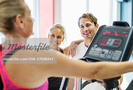 Friends looking at woman exercising on treadmill at gym Stock Photo - Premium Royalty-Free, Image code: 698-07588343