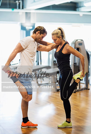 Friends doing stretching exercise together at gym Stock Photo - Premium Royalty-Free, Image code: 698-07588348