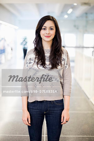 Portrait of confident female university student at college corridor Stock Photo - Premium Royalty-Free, Image code: 698-07588354