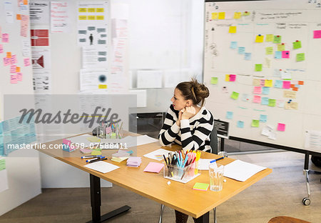 Businesswoman looking at reminders in creative office Stock Photo - Premium Royalty-Free, Image code: 698-07588411