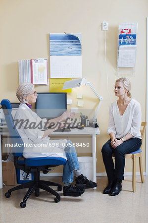 Full length of senior female doctor talking with woman in clinic Stock Photo - Premium Royalty-Free, Image code: 698-07588450