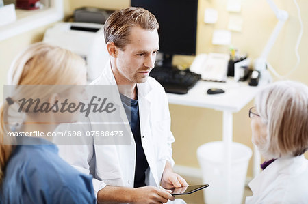 Doctors and nurse with digital tablet discussing in hospital Stock Photo - Premium Royalty-Free, Image code: 698-07588473