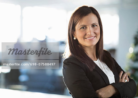 Portrait of confident businesswoman standing arms crossed in office Stock Photo - Premium Royalty-Free, Image code: 698-07588497