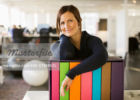 Portrait of confident businesswoman leaning on folder rack in office Stock Photo - Premium Royalty-Free, Image code: 698-07588531