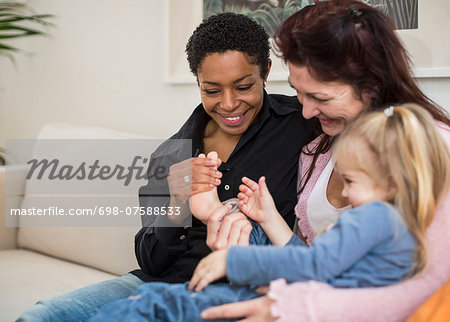 Happy lesbian couple with girl in living room Stock Photo - Premium Royalty-Free, Image code: 698-07588533
