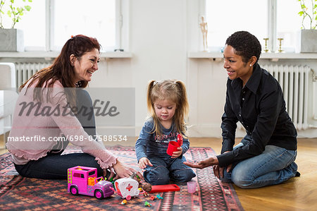 Happy lesbian couple playing with girl at home Stock Photo - Premium Royalty-Free, Image code: 698-07588534