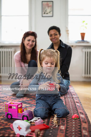 Lesbian couple looking at girl playing with toys in living room Stock Photo - Premium Royalty-Free, Image code: 698-07588535