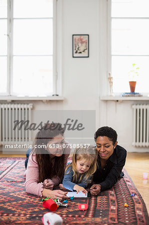 Girl and lesbian couple using digital tablet in living room Stock Photo - Premium Royalty-Free, Image code: 698-07588537