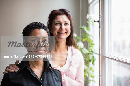 Portrait of smiling lesbian couple by window at home Stock Photo - Premium Royalty-Free, Image code: 698-07588539