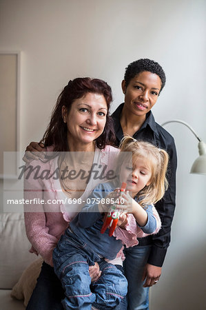 Portrait of lesbian couple with girl at home Stock Photo - Premium Royalty-Free, Image code: 698-07588540