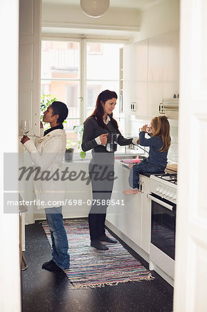Full length of lesbian couple with girl in kitchen Stock Photo - Premium Royalty-Free, Image code: 698-07588541