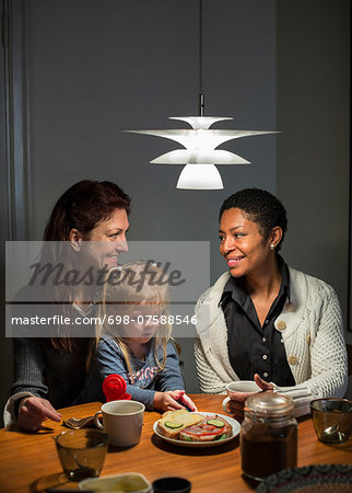 Lesbian couple and girl having breakfast at dining table Stock Photo - Premium Royalty-Free, Image code: 698-07588546