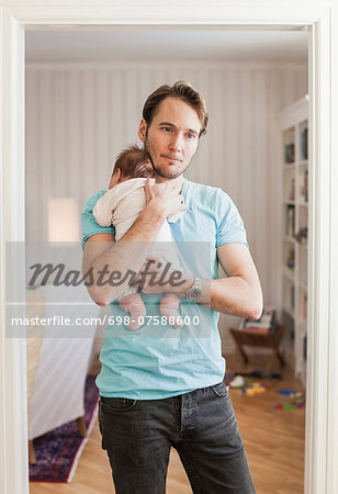 Thoughtful man carrying baby at doorway Stock Photo - Premium Royalty-Free, Image code: 698-07588600