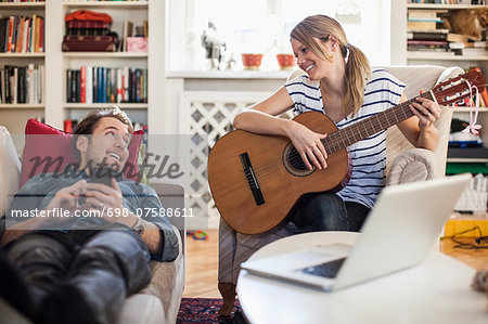 Happy woman playing guitar for man at home Stock Photo - Premium Royalty-Free, Image code: 698-07588611