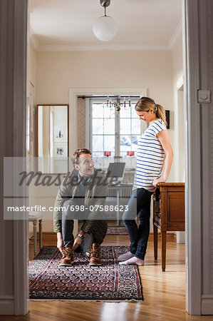Man wearing shoes while looking at woman in house Stock Photo - Premium Royalty-Free, Image code: 698-07588623