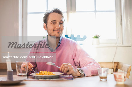 Portrait of man smiling while eating pasta Stock Photo - Premium Royalty-Free, Image code: 698-07588627