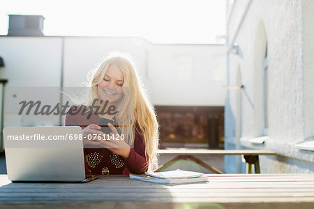 Happy teenage girl using mobile phone with laptop on table outdoors Stock Photo - Premium Royalty-Free, Image code: 698-07611420