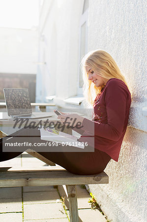 Side view of high school girl using mobile phone at picnic table Stock Photo - Premium Royalty-Free, Image code: 698-07611426