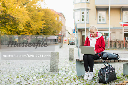 Full length of teenage girl using laptop on bench by city street Stock Photo - Premium Royalty-Free, Image code: 698-07611444