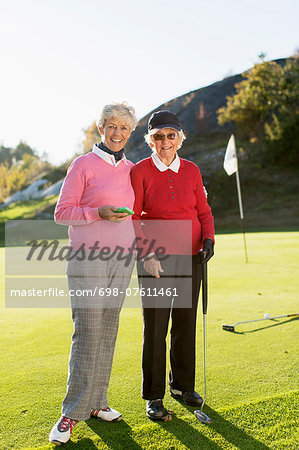 Full length portrait of senior female golfers standing on golf course Stock Photo - Premium Royalty-Free, Image code: 698-07611461