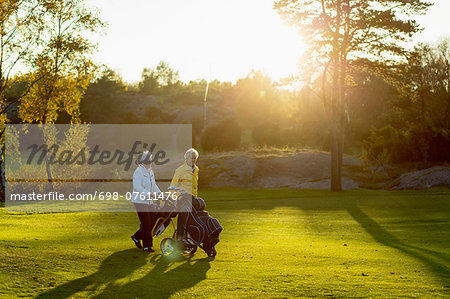 Senior women walking with golf bags on grassy area Stock Photo - Premium Royalty-Free, Image code: 698-07611476