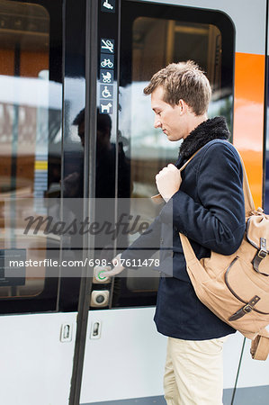 Side view of young businessman pressing door button while boarding train Stock Photo - Premium Royalty-Free, Image code: 698-07611478