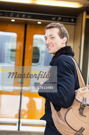 Portrait of smiling young businessman with backpack on railroad station